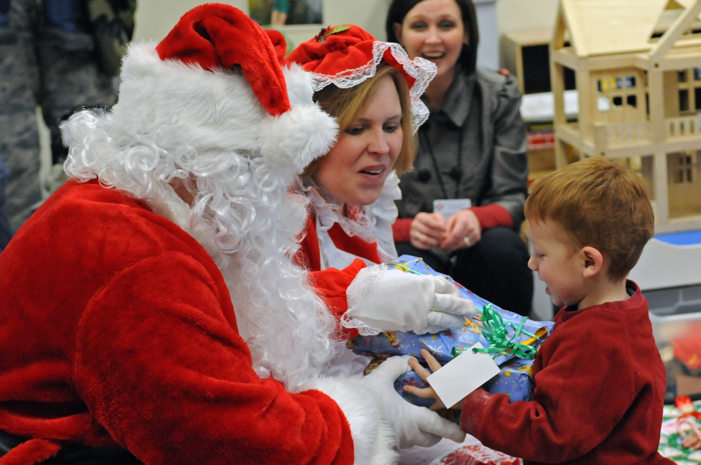 Santa and Mrs. Claus give Thad Anderson his present at the Youth and Family Services Child Care Center in Rapid City, S.D., Dec. 18, 2008. Students received many varieties of gifts due to the generosity of active duty members and their families. (US Air Force photo/Airman 1st Class Corey Hook)(Released)
